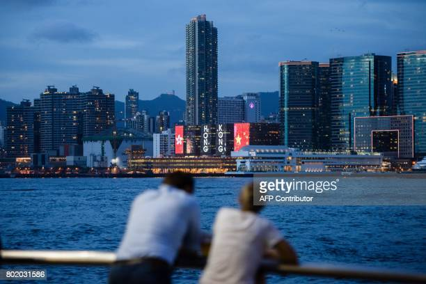 Two friends chat in front of a view of Victoria Harbour and a light display commemorating the 20th anniversary of the city's handover from British to...