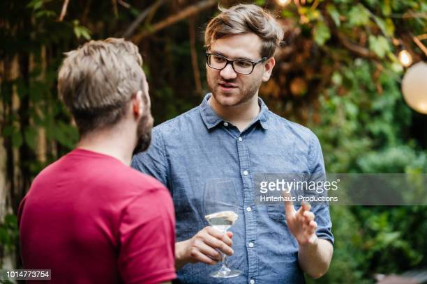 two friends chatting and drinking at bbq - blonde glasses stock-fotos und bilder