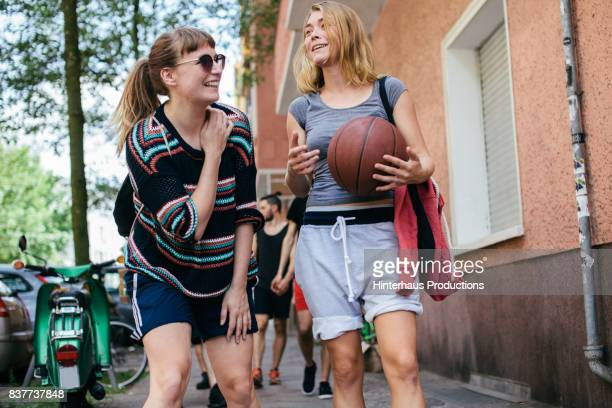 Two Friends Chatting And Laughing After Playing Basketball