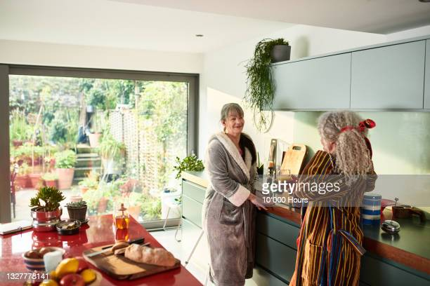 two friends chatting and making breakfast - greater london stock pictures, royalty-free photos & images