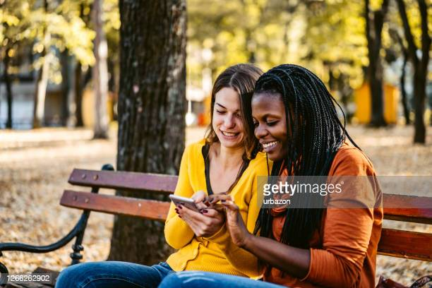two friends checking social media on phone - article stock pictures, royalty-free photos & images
