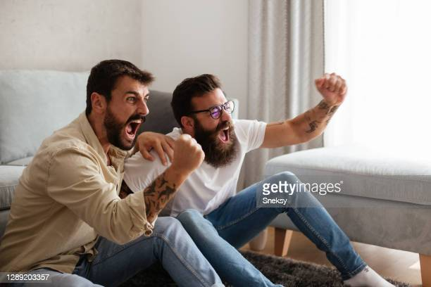 two friends cheering, watching sport event on tv. - match sport stock pictures, royalty-free photos & images
