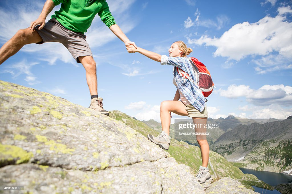 Two friends climbing a rock, one helping the other-Summer : Stock Photo