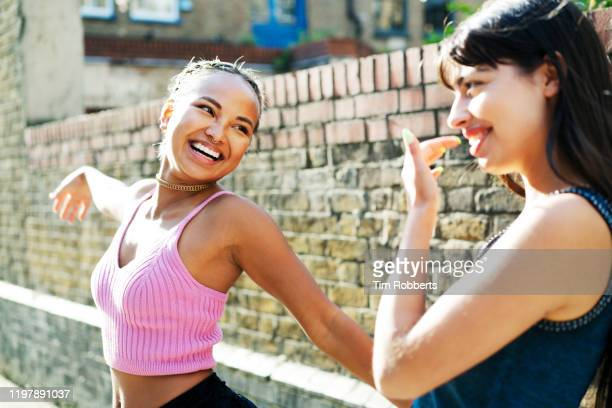 two friends dancing on street - only women stock pictures, royalty-free photos & images