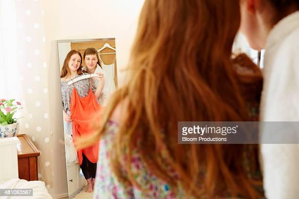 two friends deciding what clothes to wear - anprobieren stock-fotos und bilder