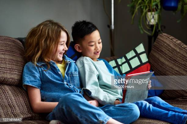 two friends doing home school work together - wellbeing stock pictures, royalty-free photos & images