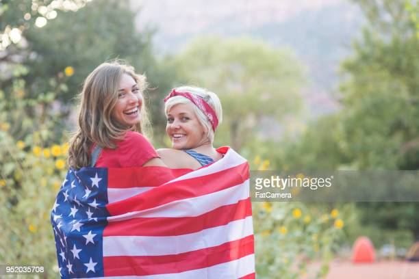 two friends drape themselves in an american flag outside - political party stock pictures, royalty-free photos & images
