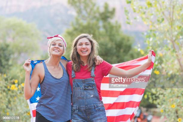 two friends drape themselves in an american flag outside - independence day holiday stock pictures, royalty-free photos & images