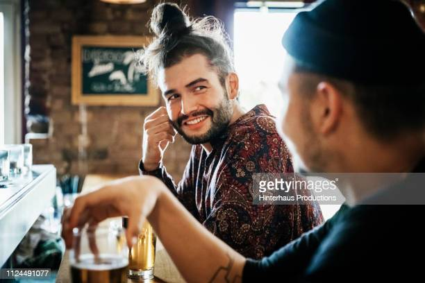 two friends drinking at bar together - hipster stock-fotos und bilder