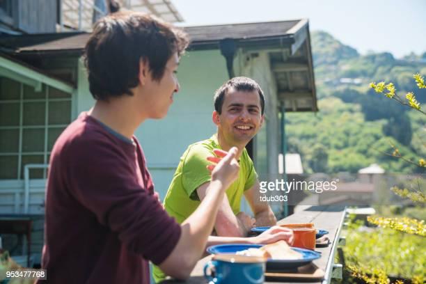 Zwei Freunde beim Frühstück auf der Terrasse in einer Herberge in den Bergen