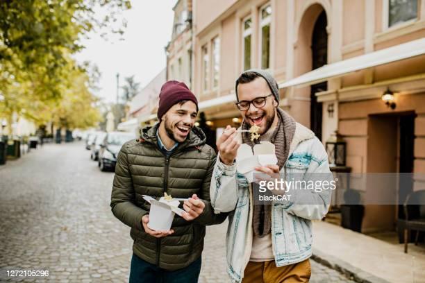 twee vrienden die snel voedsel in openlucht eten - gay couple stockfoto's en -beelden