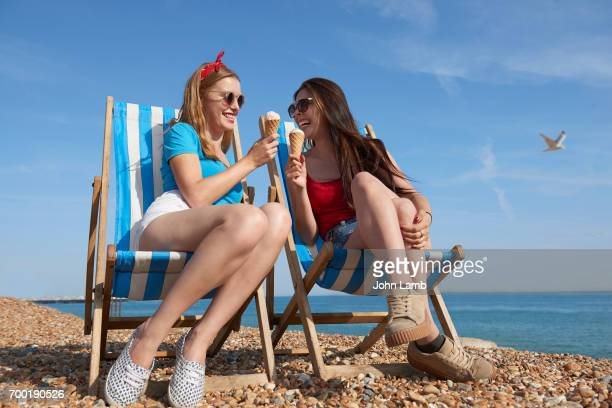 two friends eating ice cream on brighton beach - brighton england stock pictures, royalty-free photos & images