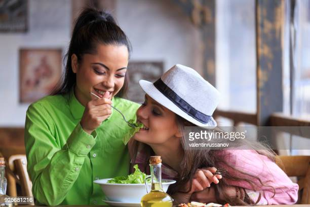 two friends eating salad and pizza in restaurant - lesbian date stock pictures, royalty-free photos & images