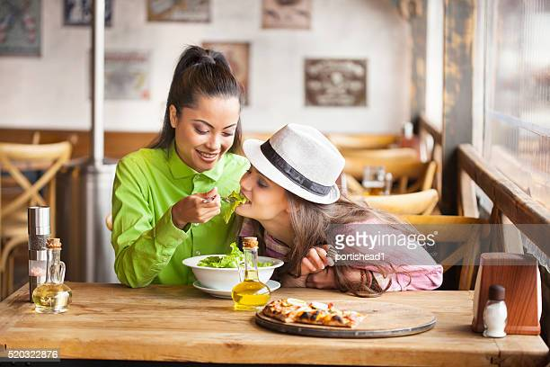 Two friends eating salad at restaurant