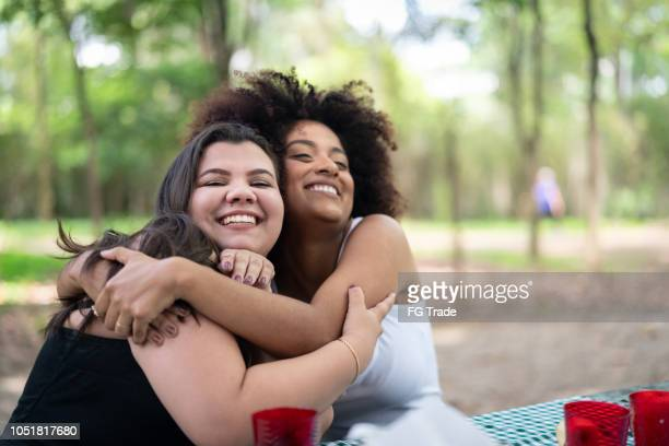 two friends embracing at picnic party - affectionate stock pictures, royalty-free photos & images