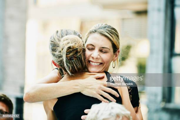 two friends embracing before dinner party on summer evening - incidental people stock pictures, royalty-free photos & images