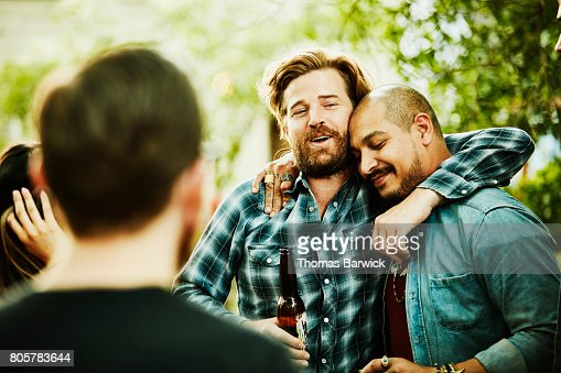 Two friends embracing during backyard party on summer evening