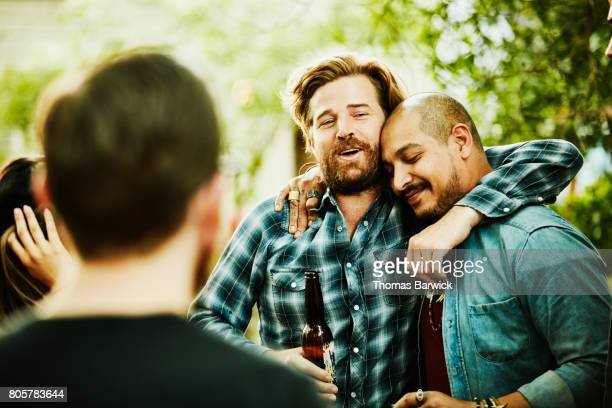 two friends embracing during backyard party on summer evening - arm around stock pictures, royalty-free photos & images