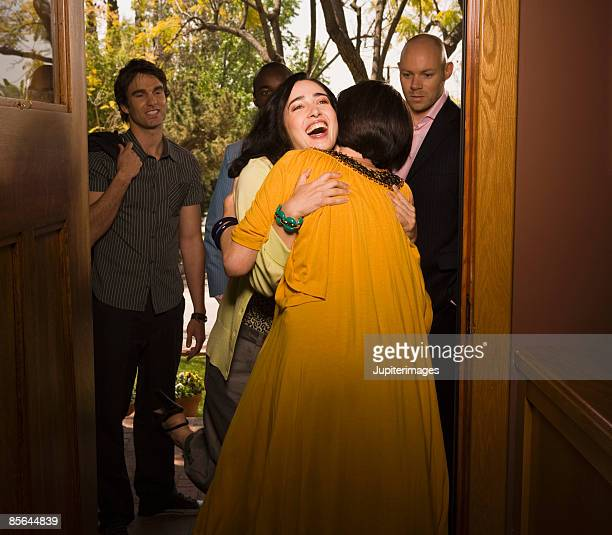 two friends embracing - welcoming guests stock photos and pictures