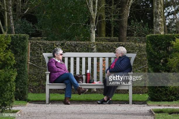 Two friends enjoy a hot drink together on a bench but at a safe distance during a visit to the gardens at Hanbury Hall in central England on March 21...