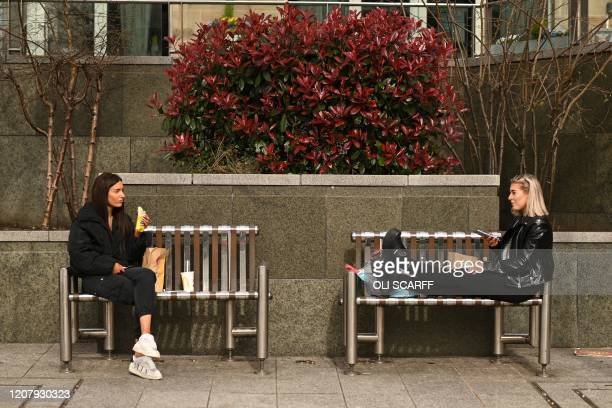 Two friends enjoy their lunch together at a safe distance in central Leeds on March 21 a day after the British government said it would help cover...