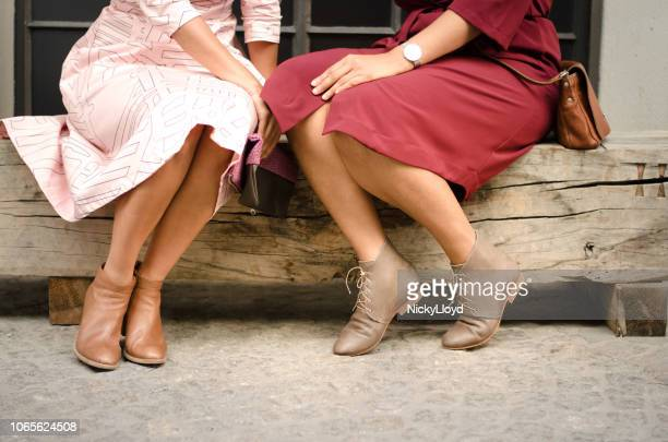 two friends enjoying time together deep in conversation - black skirt stock pictures, royalty-free photos & images