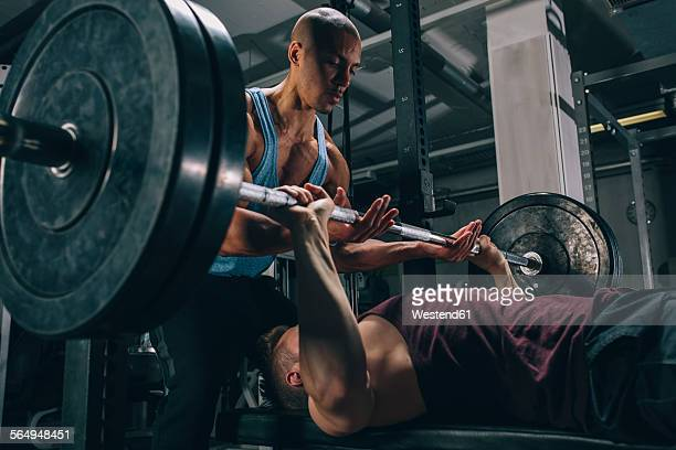 two friends exercising bench press in gym - bodybuilding stock-fotos und bilder