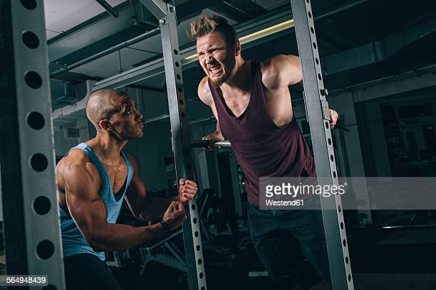 Two friends exercising dips at power rack in gym