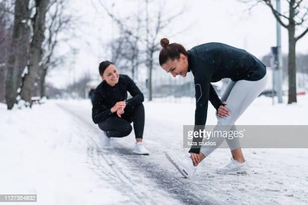 twee vrienden uitoefenen in de sneeuw - winter sport stockfoto's en -beelden