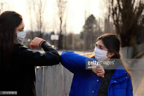 two friends greeting during pandemic - elbow bump stock pictures, royalty-free photos & images