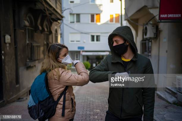 two friends greeting during pandemic - coronavirus winter stock pictures, royalty-free photos & images