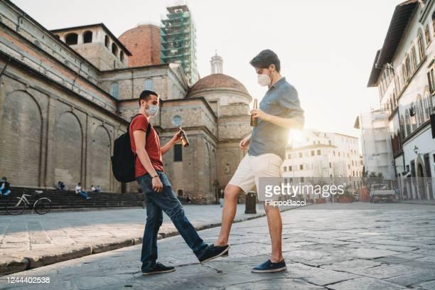 zwei freunde grüßen sich gegenseitig, tippen auf die füße und trinken bier - corona beer stock-fotos und bilder