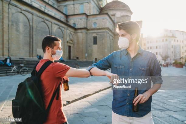 zwei freunde grüßen sich gegenseitig mit dem ellenbogen - corona beer stock-fotos und bilder