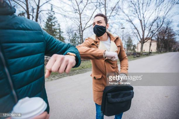 two friends greeting with alternative handshake - spreading stock pictures, royalty-free photos & images