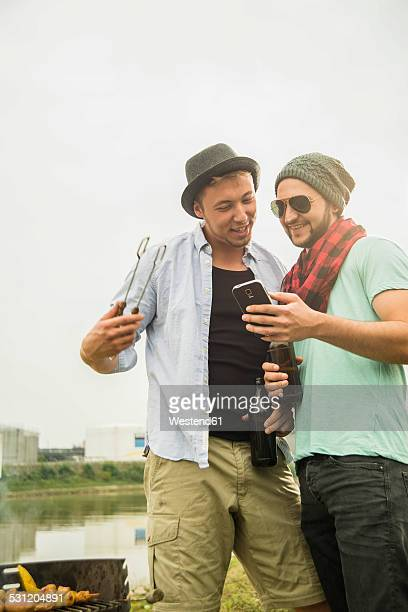 Two friends having a barbecue and looking at cell phone outdoors