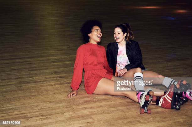two friends having fun at roller disco - roller rink stock photos and pictures