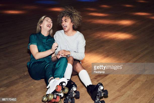 two friends having fun at roller disco - ridere foto e immagini stock