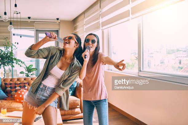 two friends having fun singing together - karaoke stock pictures, royalty-free photos & images