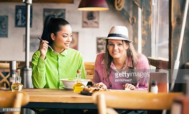 Two friends having lunch break at restaurant
