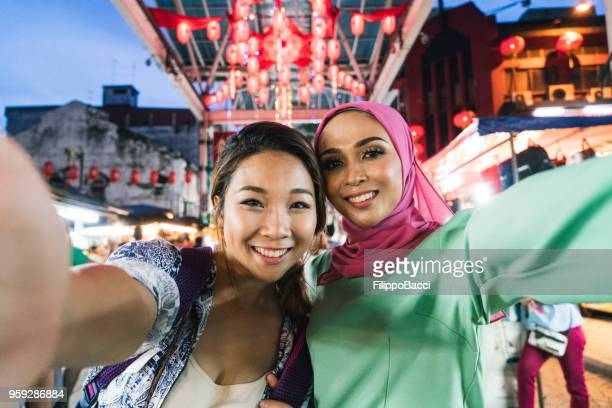 two friends having selfie together at the market - malaysia stock pictures, royalty-free photos & images