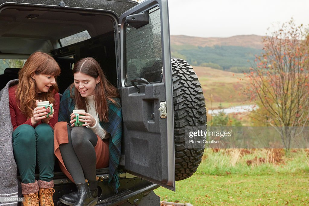 Two friends having tea in the back of their car : Foto de stock