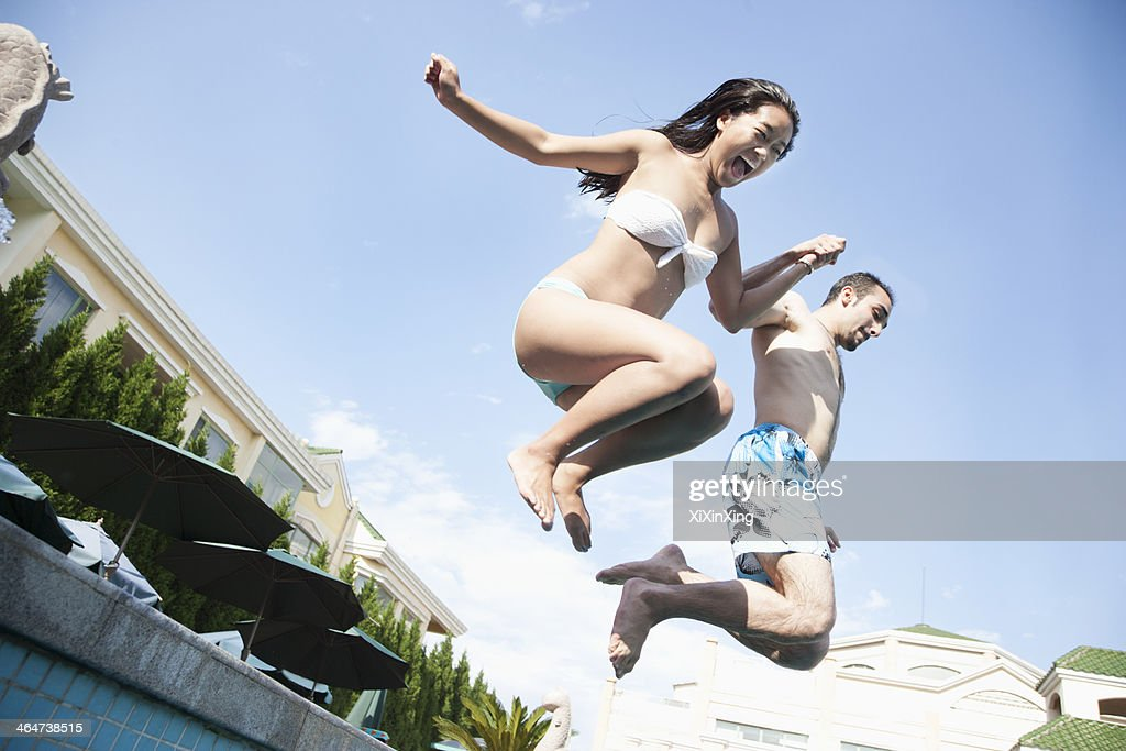 Two friends holding hands and jumping into a pool, mid-air : Stock Photo