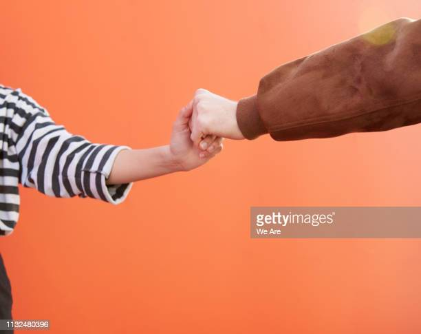 two friends holding hands. - colour block stock pictures, royalty-free photos & images