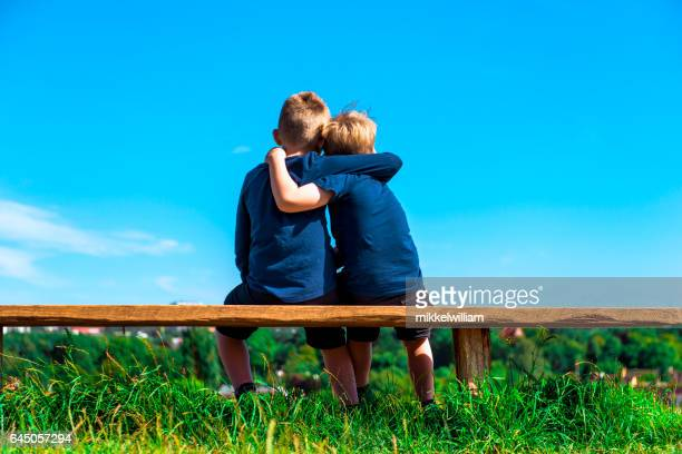 Two friends hug each other while sitting on a bench outside
