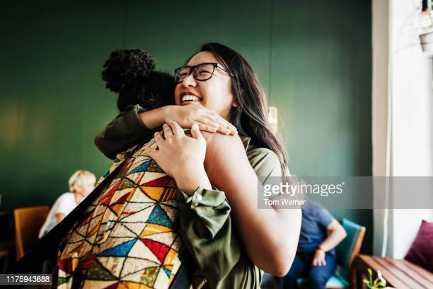 two friends hugging in cafe - embracing stock pictures, royalty-free photos & images