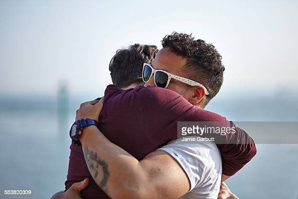 Two friends hugging smiling straight at camera