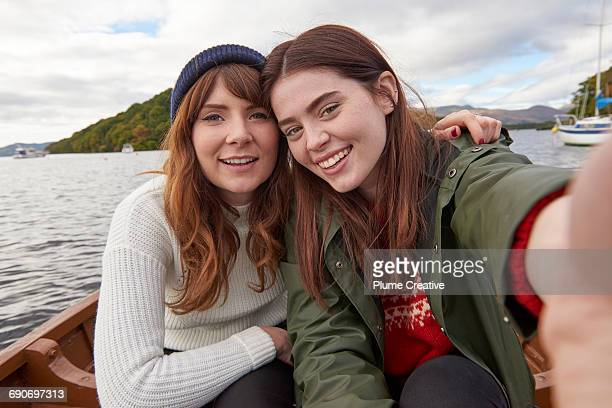 two friends in a row boat taking a selfie - only young women stock pictures, royalty-free photos & images