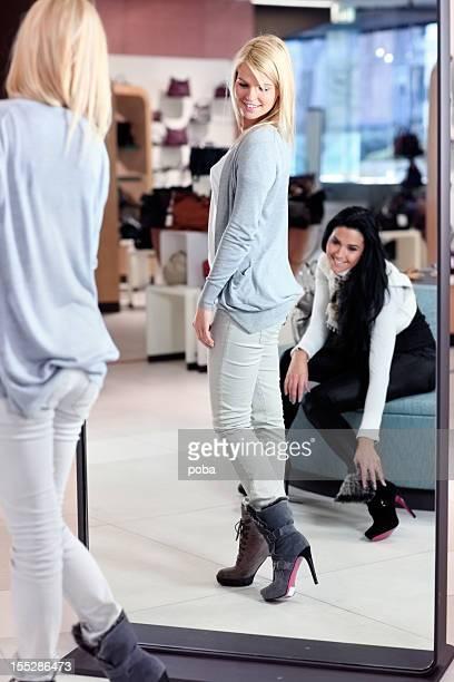 Zwei Freunde im Kaufhaus, die im neuen Schuh