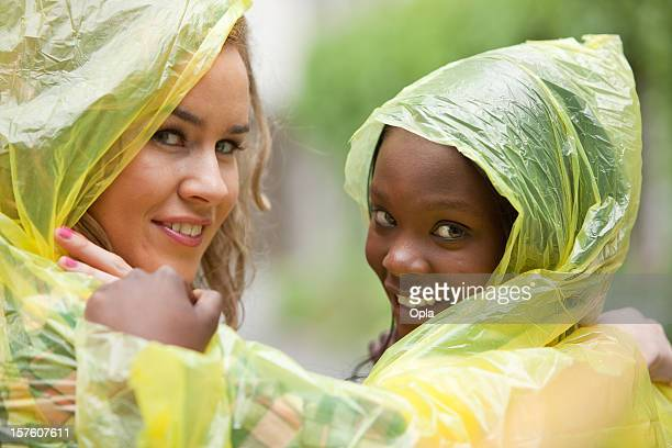 Two friends in raincoats smiling