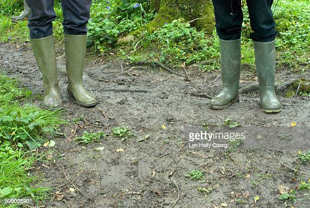 two friends in rubber boots on muddy path - lyn holly coorg stock pictures, royalty-free photos & images